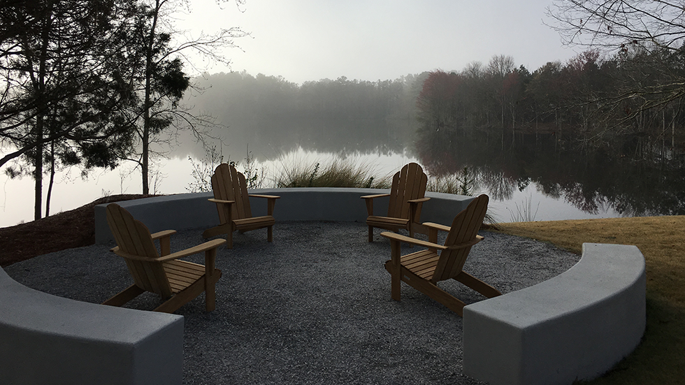 small seating area at the edge of a foggy lake with seat walls and adirondack chairs